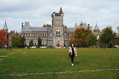 A smiling student walks across U of T's front campus lawn. University College is behind her.