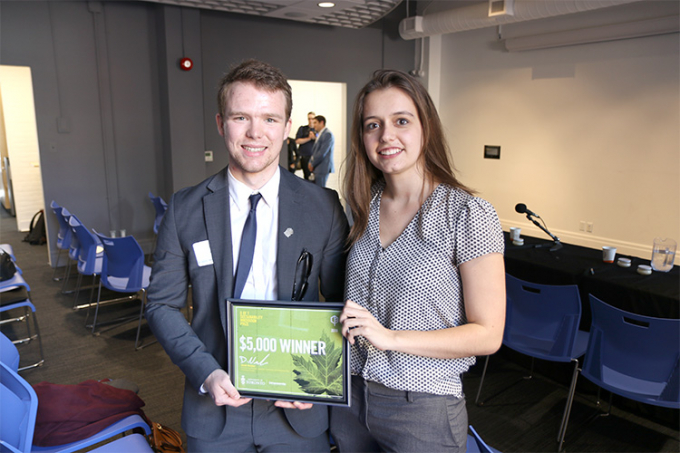 John Russell and Leanna Smid holding an award together.