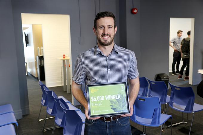 Daniel McKee holding an award.