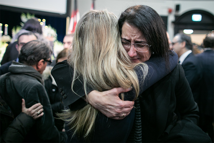 Two people embrace each other with a hug in mourning.