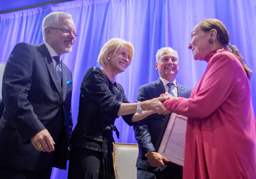 ustice Abella (right) is formally presented with the Rose Wolfe Distinguished Alumni Award for 2019 by (from left) Scott MacKendrick, immediate past president of the U of T Alumni Association, Chancellor Rose Patten and President Meric Gertler.