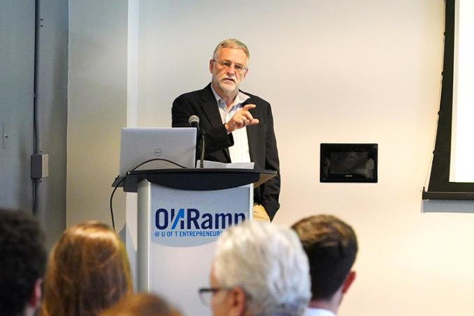 John Robinson presenting at a podium.