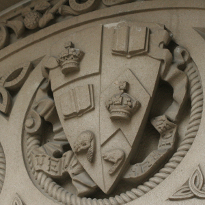 U of T coat of arms in stone on a building.