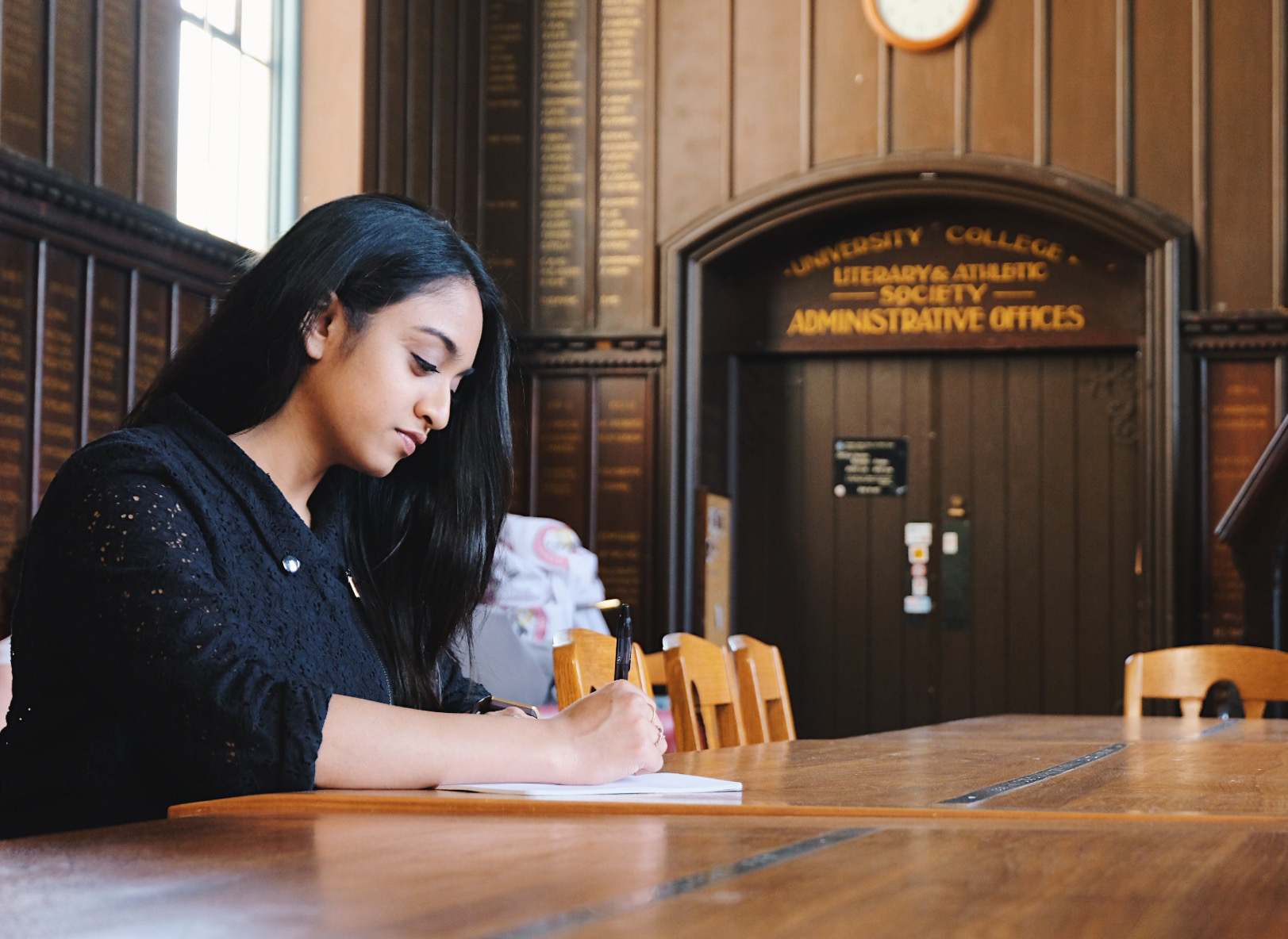 A student writing in a U of T Library.