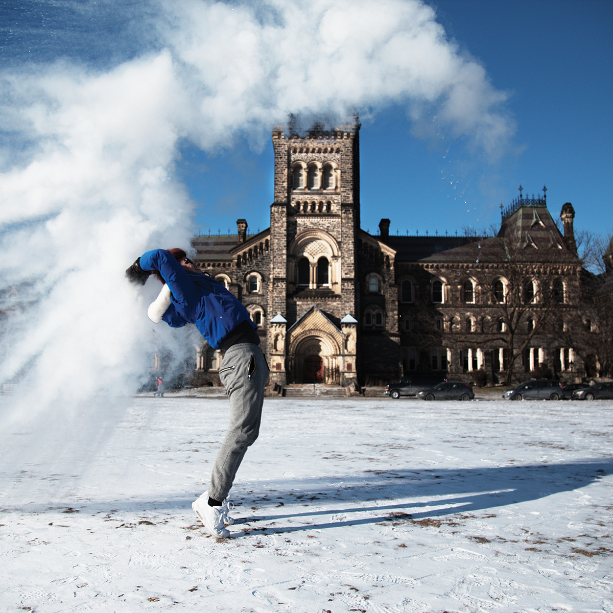 Student playing with snow in front campus