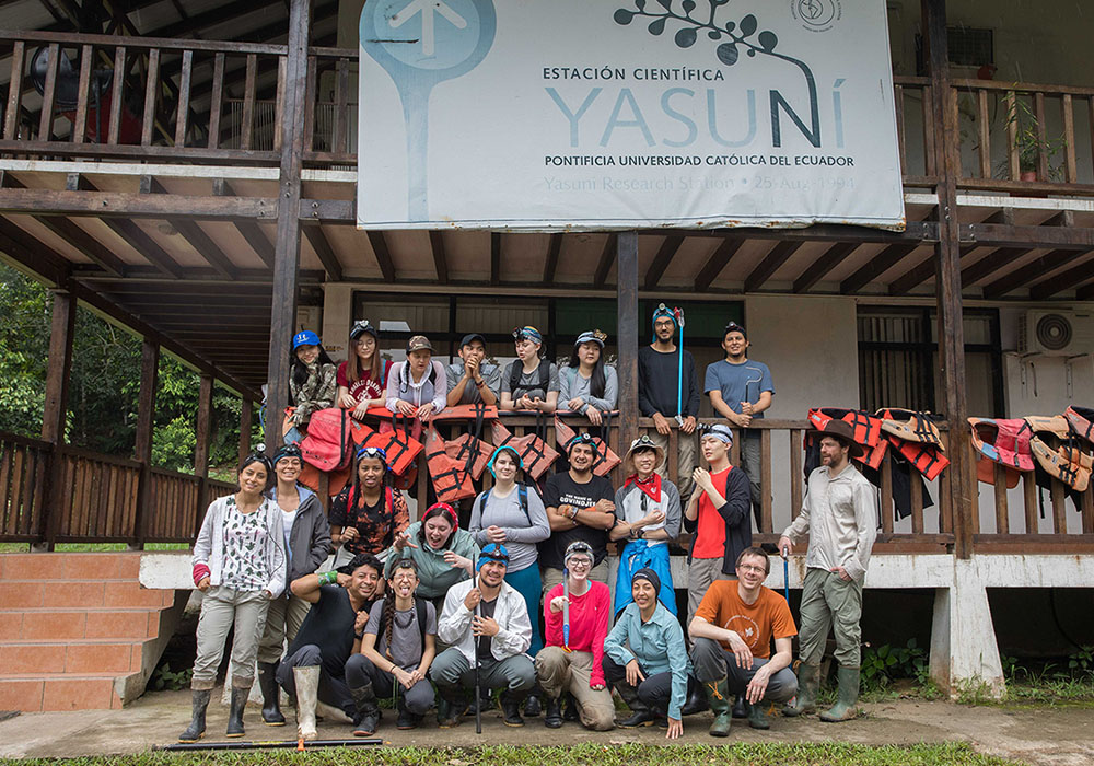 A group of undergraduate students and instructors pose in front of a two-storey wooden building at the Yasuni Research Station