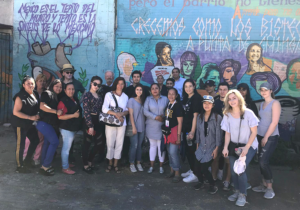 students in Mexico in front of a wall mural