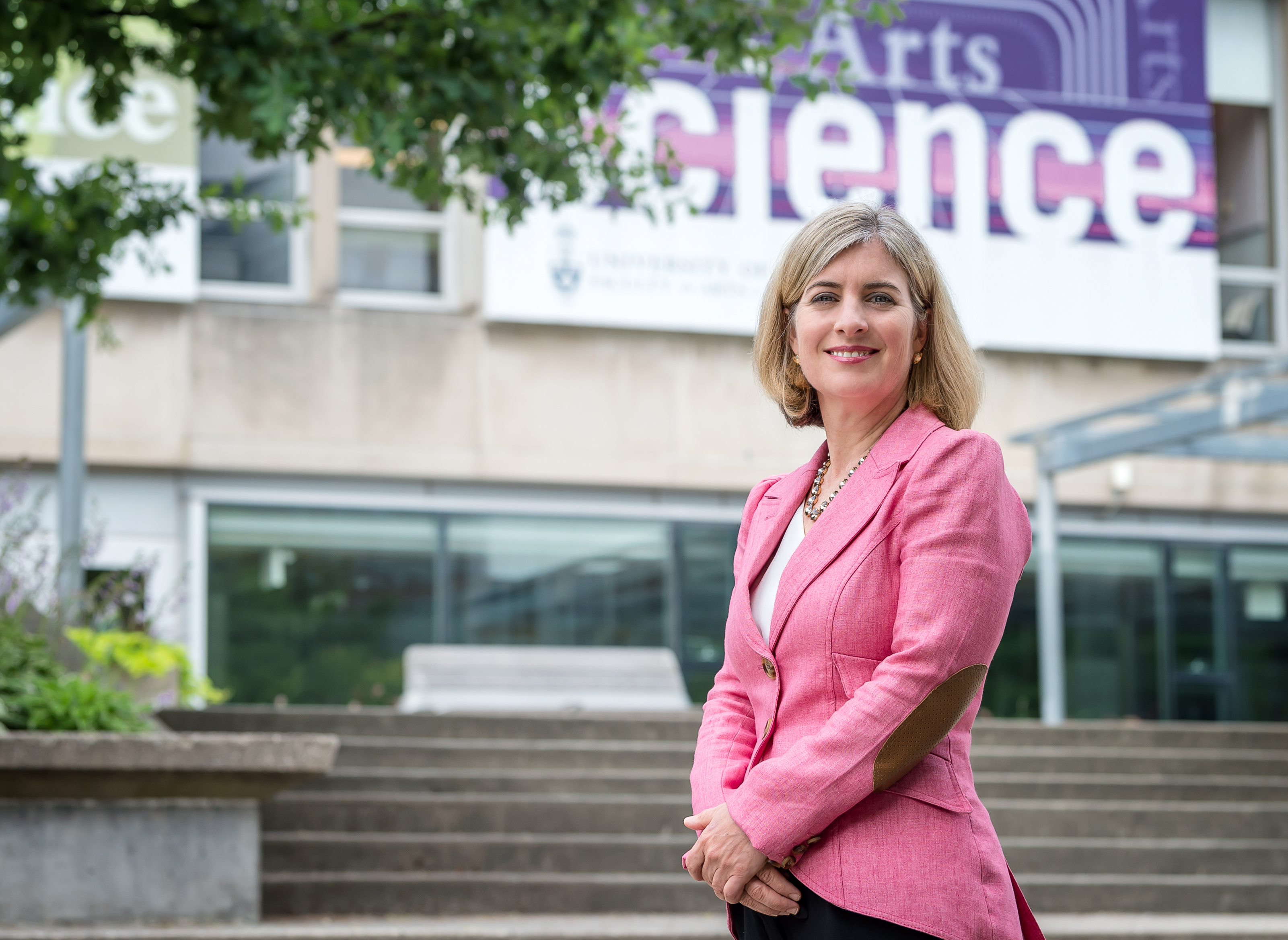 Arts & Science Dean Melanie Woodin standing in front of Sidney Smith Building