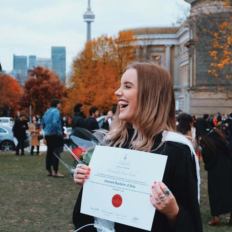 student happily holds up her diploma during convocation