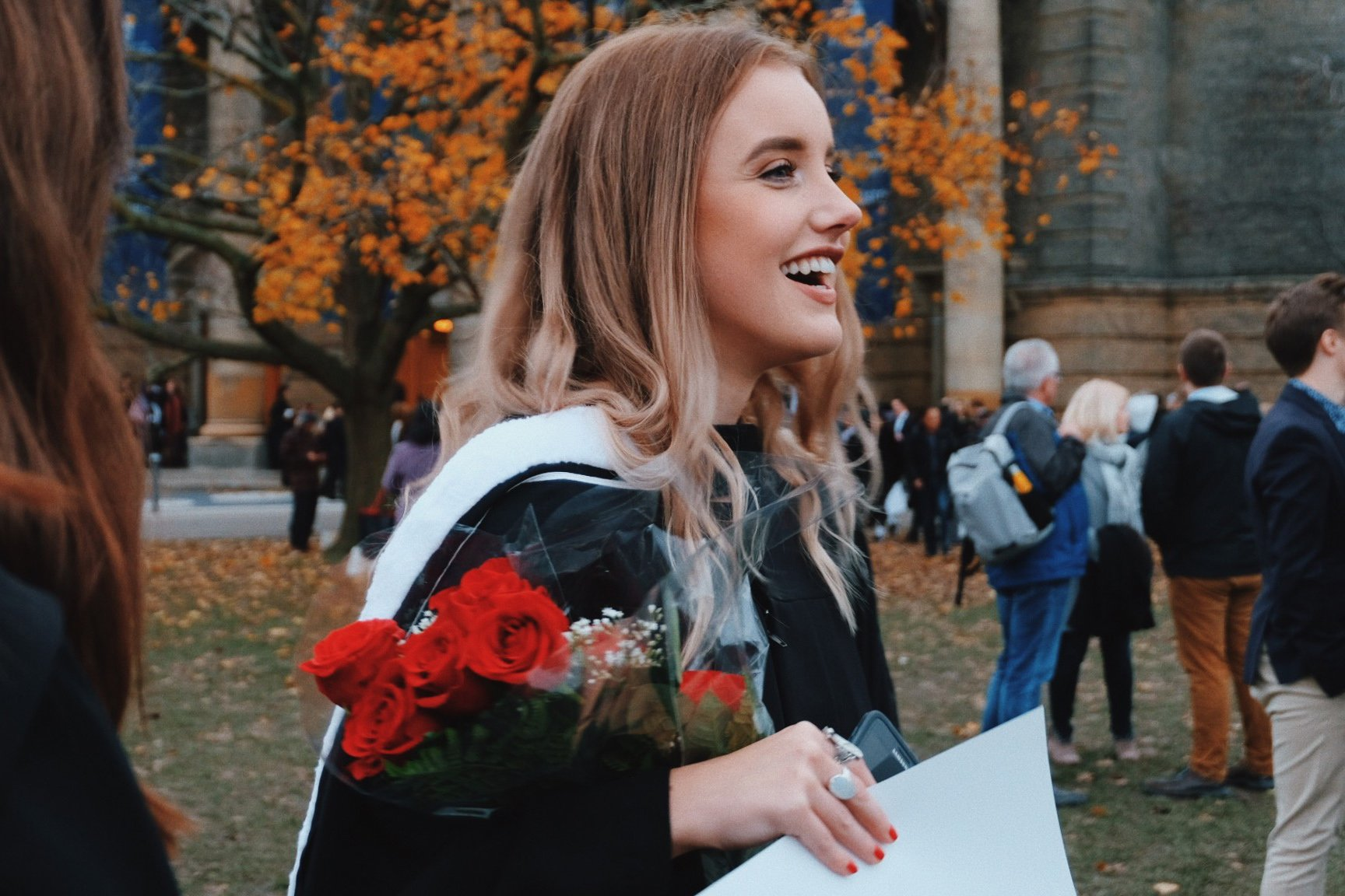 Student holding flowers at convocation ceremony