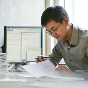 A person reviewing paperwork beside a computer.