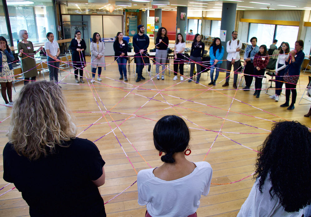 Symposium attendees stand in a circle during group reflection activity