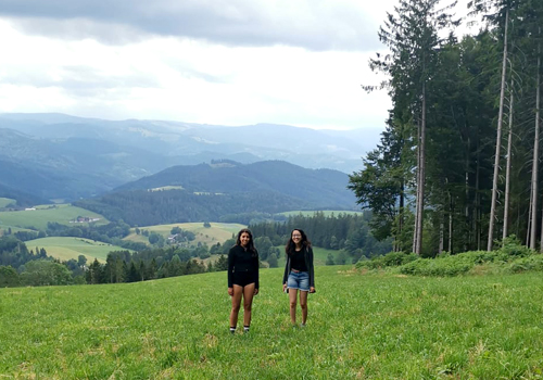 Savannah Bein and Tanvi Ghokale stand in a lush green field, beside a forest on a cloudy day.