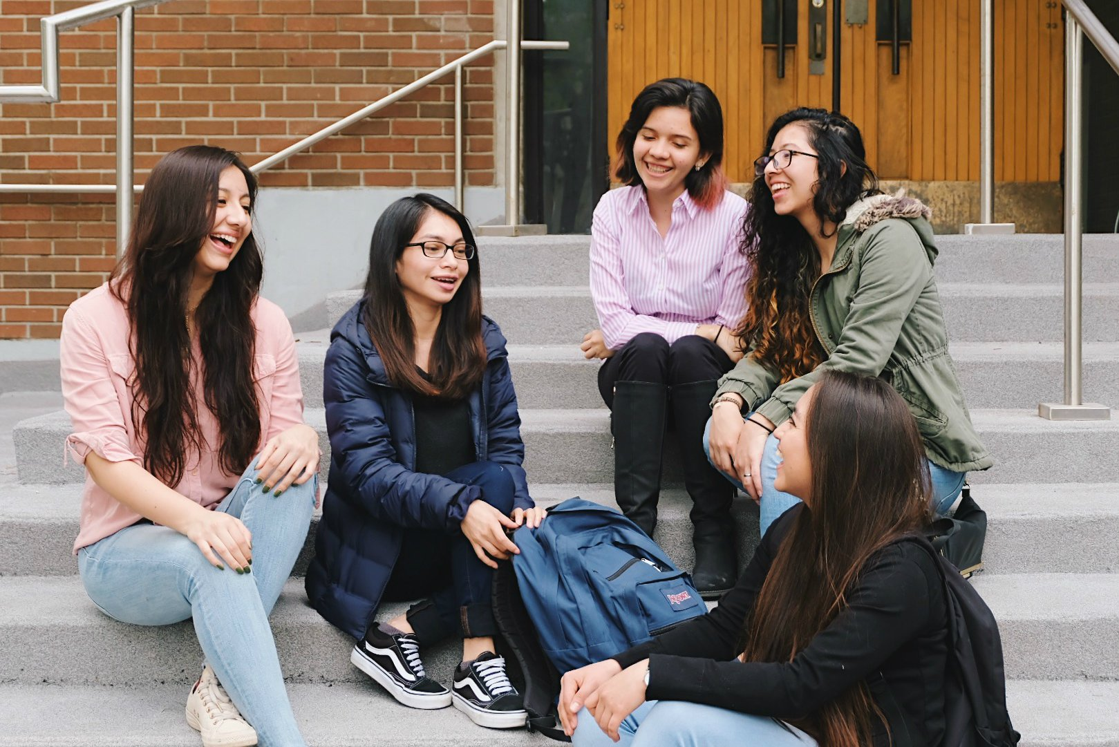 Group of female students sitting on the steps and talking to each other