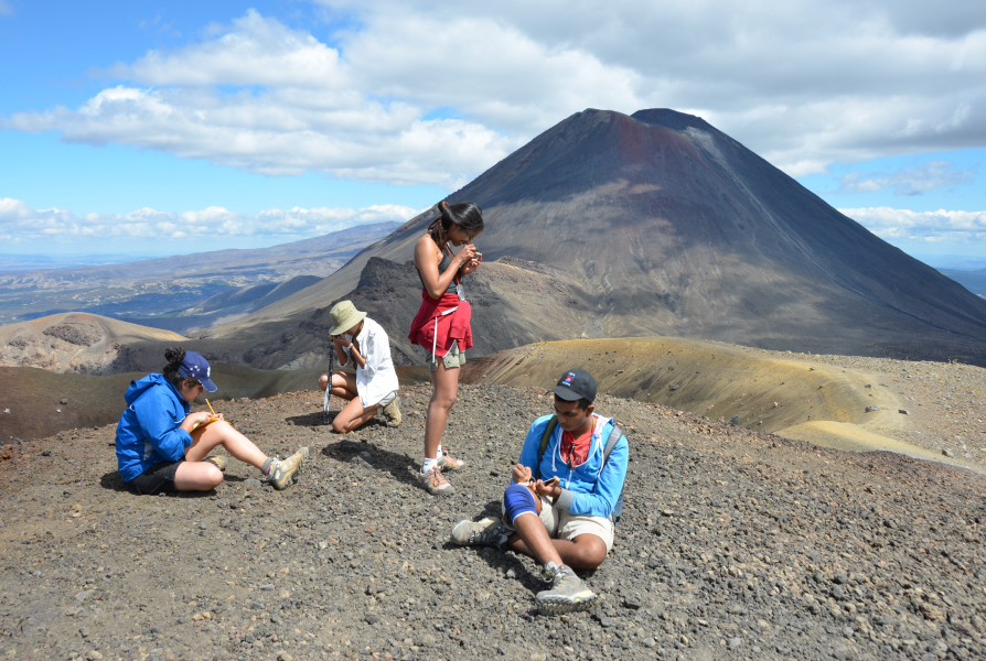 Four students studying objects on a mountain.