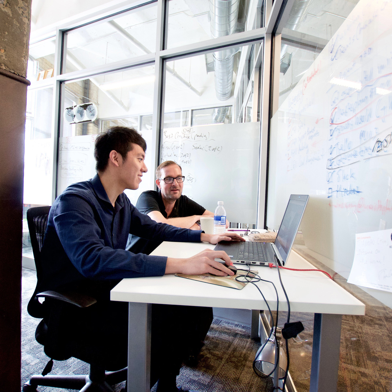Student and advisor sitting at a desk in front of an open laptop