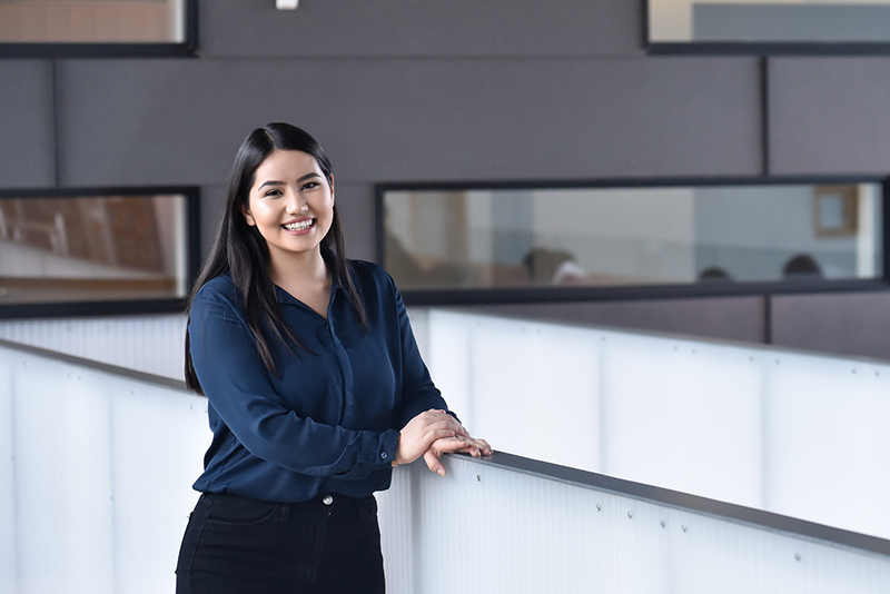 Student in business attire standing in an office space
