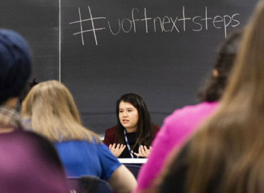 A person speaks at a Next Steps presentation. #nextsteps is written on the chalkboard in a classroom.