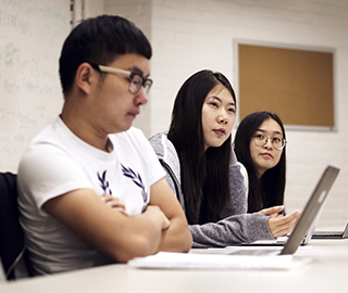Three graduate students sit side-by-side at a table during a course
