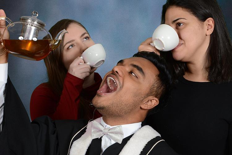 Al-amin Ahamed hoists a glass teapot overhead while two friends sip tea from white mugs