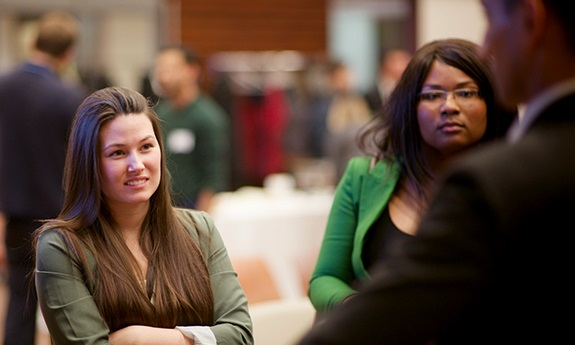 Two students listen to someone speak at a networking event