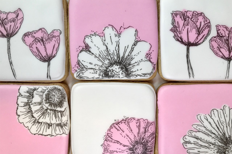 White and pink sugar cookies with beautiful paining flowers in black and white.