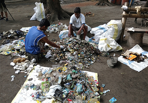 Two men crouch on the ground, surveying the piles of plastic they picked from a beach.