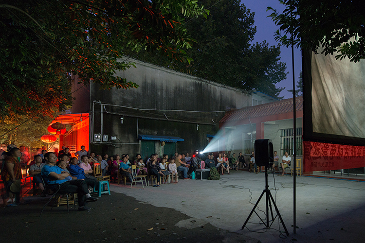 A group of people watching a film on a projector outdoors