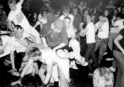 A black and white photo of a group of people in a mosh pit.