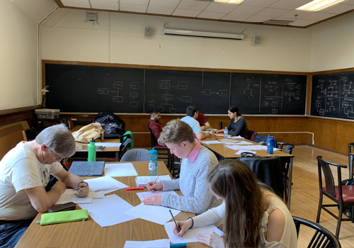 student in a classroom working at a big table together