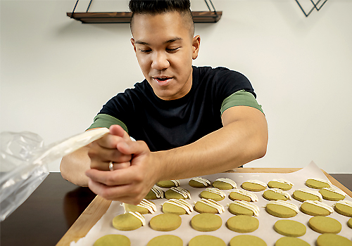 Colin Asuncion piping icing onto cookies in a zig-zag pattern.