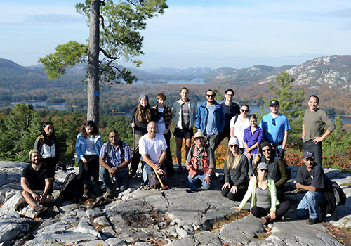 A group of students standing on a cliff with a hilled forest landscape and lakes in the background.
