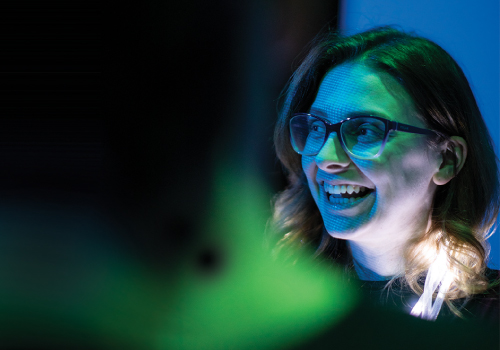 A person smiling with the reflection of a computer screen over her face.