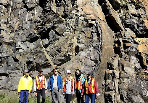 A group of students in front of a rock wall.