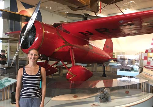 Alumna Lindsay Zier-Vogel beside a red plane.