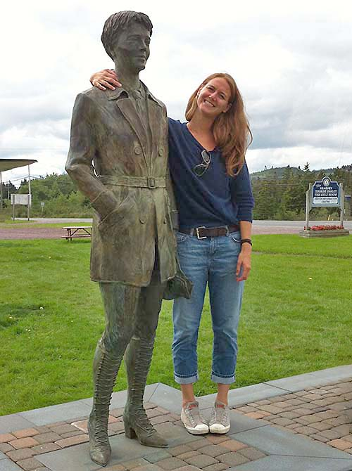 Alumna Lindsay Zier-Vogel beside a statue of a person.