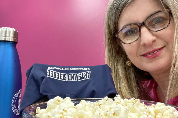 Dean Melanie Woodin poses with a bowl of popcorn, reusable water bottle and A&S sweatshirt