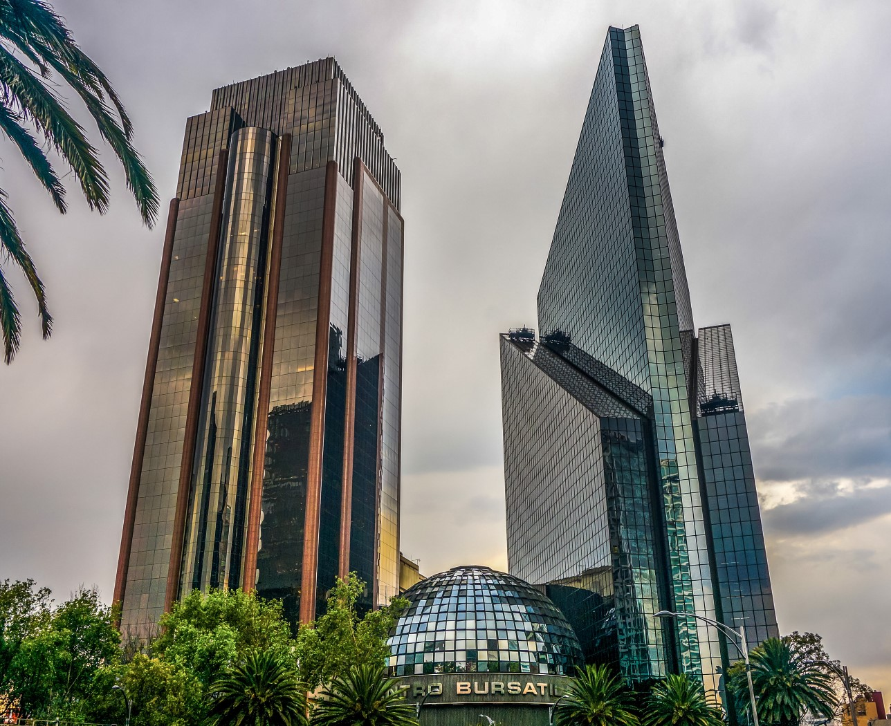 Two glass skyscrapers with a dome-shaped building between them