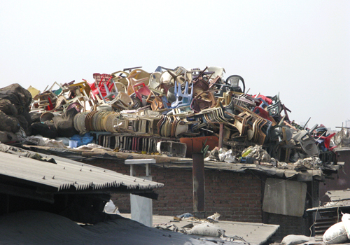A pile of plastic chairs and other waste at a recycling facility