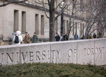 A view of a stone sign that says University of Toronto from St. George street.