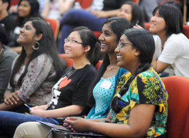 A group of students sit and smile within a lecture hall.
