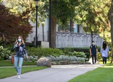 Three students walking outdoors on a summer day, all wearing masks.