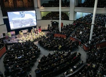A picture taken from the balcony of a full hall.