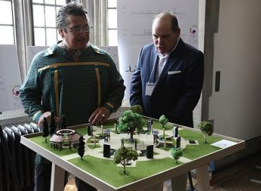 """Chief Stacey Laforme and James Bird looking over the model for a """"reconciliation grove"""""""