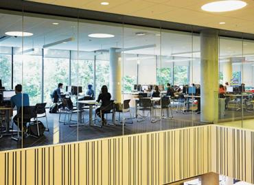 Open room with computers and students studying at U of T Mississauga