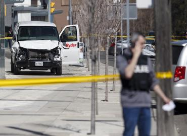 The white van used in the Yonge Street attack sits empty on the sidewalk with its driver-side door open, behind police tape