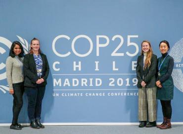 Four students stand infront of a blue wall, with large white letters, COP25 — Chile — Madrid 2019 — UN Climate Change Conference.
