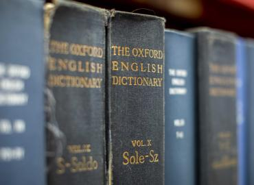 The Oxford English Dictionary on a shelf with other books