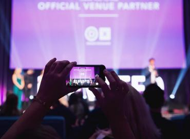 An attendee holding up a smartphone to record the stage at Elevate 2019