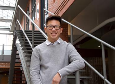 Ethan Kim in front of metal stairs at Innis College